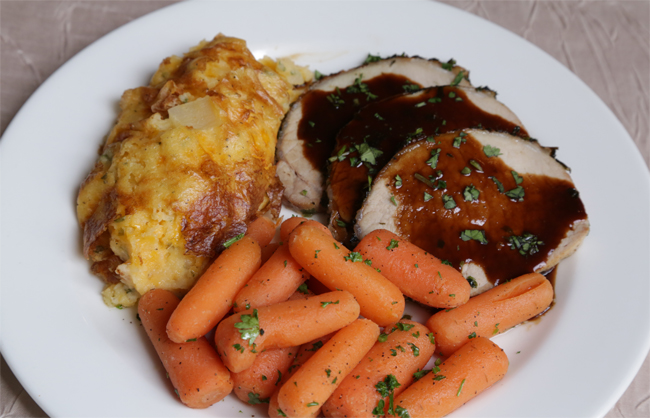 Herb Crusted Pork Loin with Twice Baked Potato Casserole and Buttered Baby Carrots